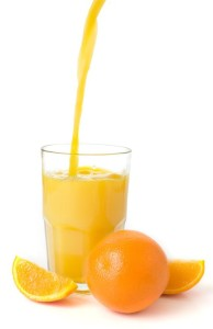 Orange Juice pouring into a glass with an orange and orange silces around.