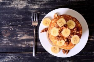 Pancakes with banana & walnut on wood background .